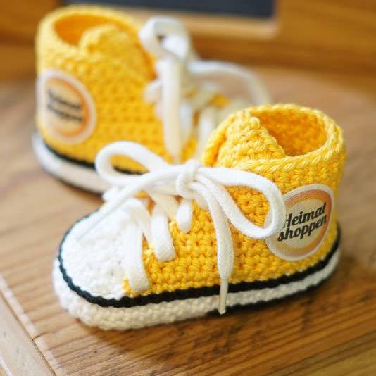 Ein gestricktes, gelbes paar Baby-Schuhe auf einem braunen Holztisch. Auf der Seite der Schuhe ist das Heimatshoppen-Logo