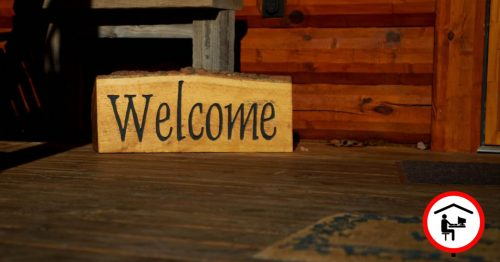 Veranda einer Holzhütte. Auf dem Boden der Veranda steht ein aus Holz geschnitztes Welcome-Schild.
