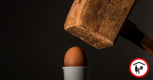 Ein großer Holzhammer befindet sich über einem braunen Ei in einem weißen Eierbecher.