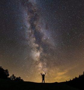 Mann steht vor dem Abendhimmel und hebt die Arme.