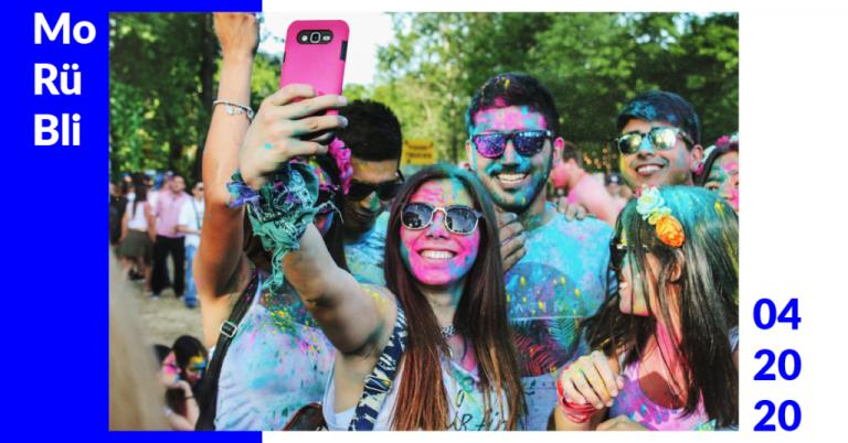 Eine Gruppe Menschen, die auf einem Festival mit verschiedenfarbigen Farbpulvern überschüttet wurden, machen ein Selfie.