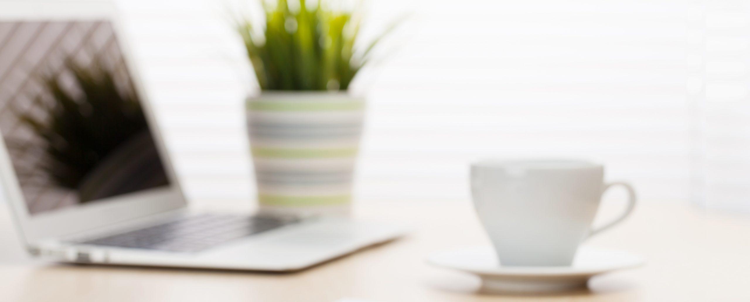 Arbeitsplatz mit Kaffeebecher, Laptop und Pflanze auf einem Tisch