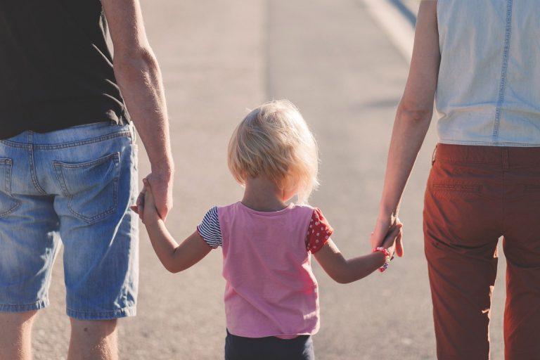 Zwei Eltern und ein Kind mit dem Rücken zur Kamera. Die Eltern halten das Kind rechts und links an den Händen.